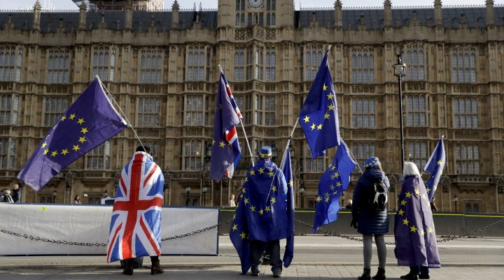 Pro-EU membership supporters hold European Union flags as they protest against Brexit across the street from the Houses of Parliament in London, Tuesday, Jan. 30, 2018. A leaked, and gloomy, economic forecast has inflamed arguments about Britain's decision to leave the European Union. Brexit-supporting politicians on Tuesday said those who released the document were trying to derail Britain's EU exit, while pro-EU lawmakers accused the government of burying bad news. (AP Photo/Matt Dunham)