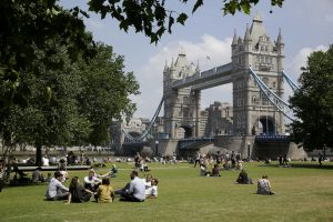 People relax in the sun during lunchtime as they sit in Potters Fields Park, backdropped by the Tower Bridge, in London, Thursday, June 28, 2018. (AP Photo/Matt Dunham)