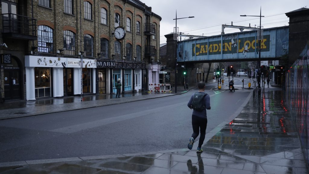 A man jogs in Camden Town, an area of London usually bustling with tourists and visitors to its market.